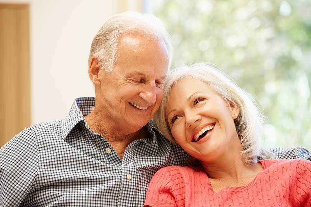 Older woman leaning against an older man and both are smiling