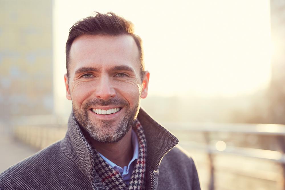 A man outside on a balcony and smiling